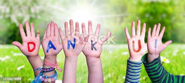 516544386 istock photo Children Hands Building Word Dank U Means Thank You, Grass Meadow 1215473988