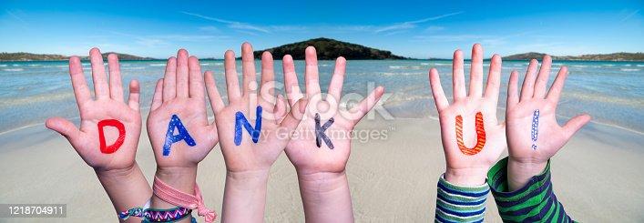 516544386 istock photo Children Hands Building Word Dank U Means Thank You, Ocean Background 1218704911