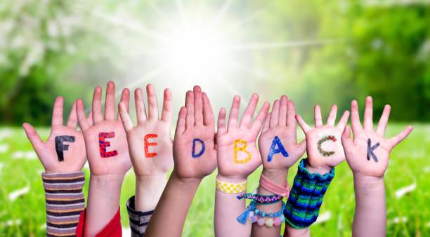 kinder hände bauen wort feedback, graswiese - feedback stock-fotos und bilder