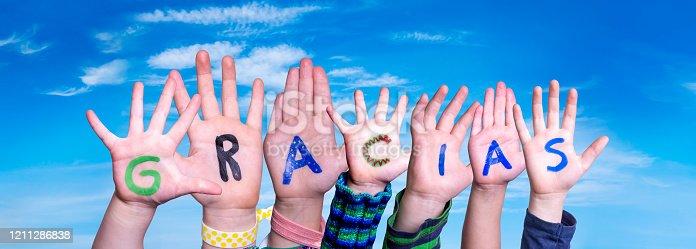 516544386 istock photo Children Hands Building Word Gracias Means Thank You, Blue Sky 1211286838