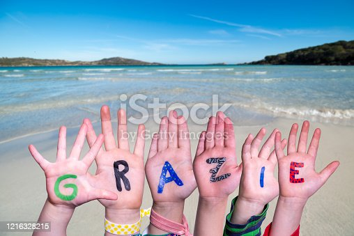 516544386 istock photo Children Hands Building Word Grazie Means Thank You, Ocean Background 1216328215