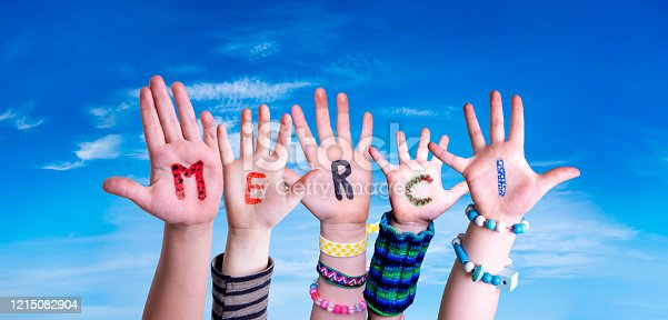 516544386 istock photo Children Hands Building Word Merci Means Thank You, Blue Sky 1215082904