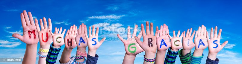 516544386 istock photo Children Hands Building Word Muchas Gracias Means Thank You, Blue Sky 1215082566