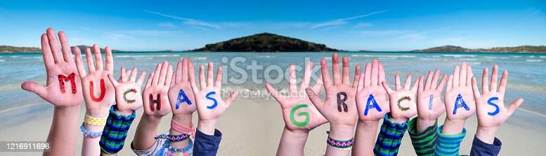 516544386 istock photo Children Hands Building Word Muchas Gracias Means Thank You, Ocean Background 1216911696