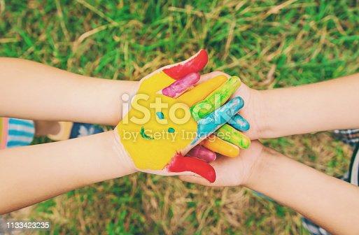 istock children hands in colors. Summer photo. Selective focus. 1133423235