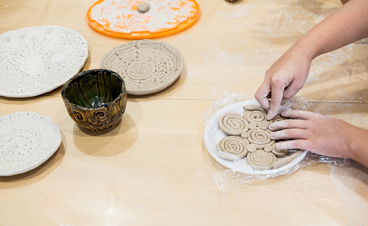 Children hands that mold from clay. Children creativity. Crafts from clay. Clay modeling courses