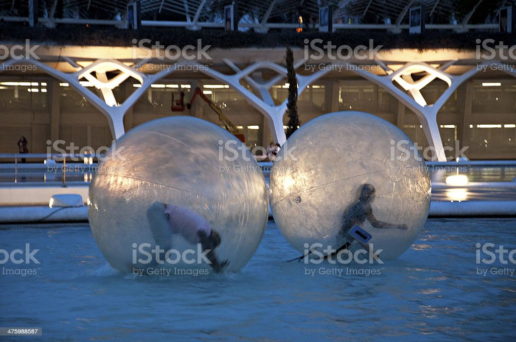 Children have fun in huge zorbing ball on water stock photo