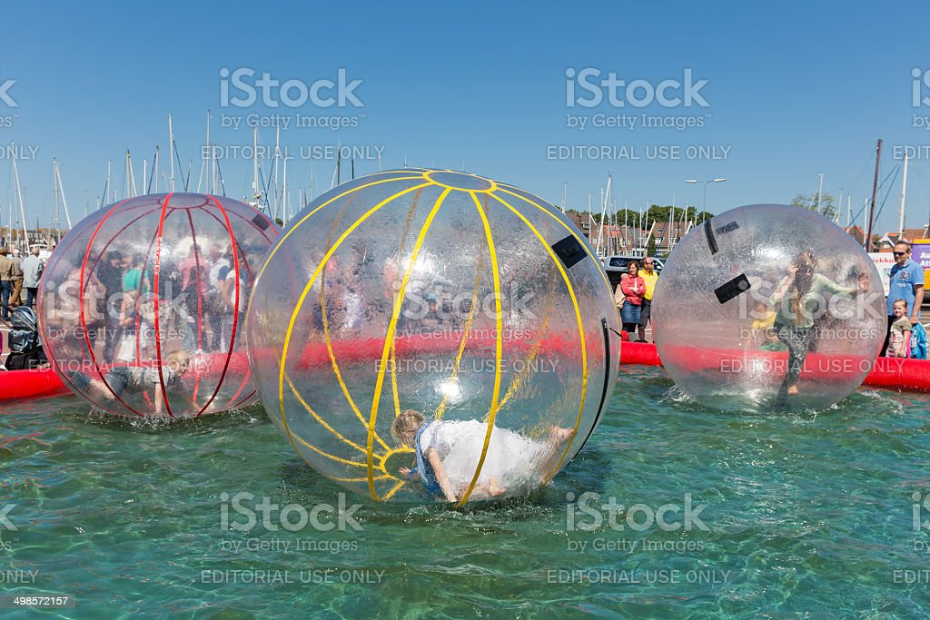 Children have fun inside plastic balloons on the water stock photo