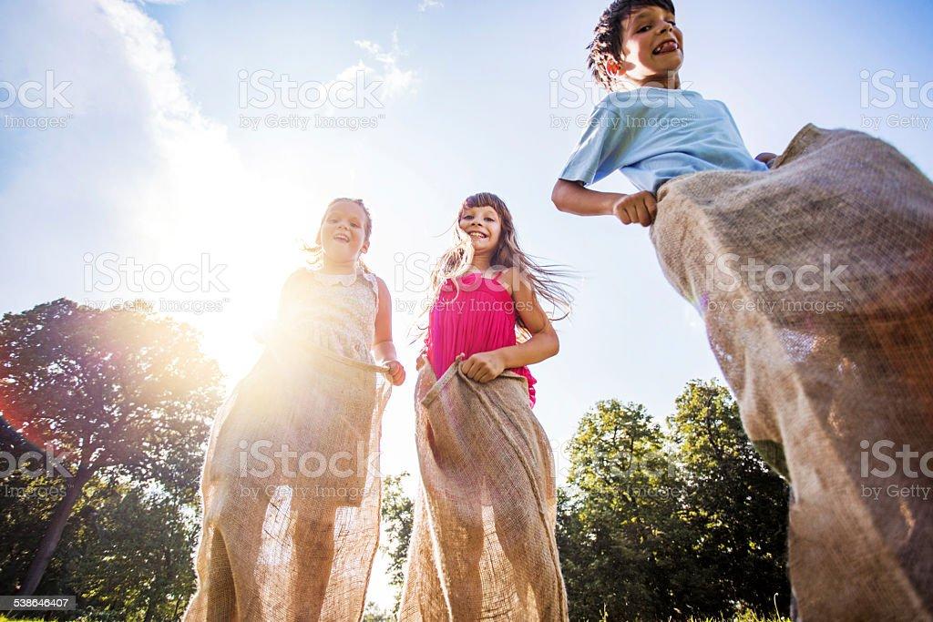 Children having a sack race outdoors. stock photo