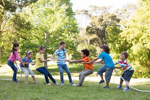 istock Children having a tug of war in park 471114276