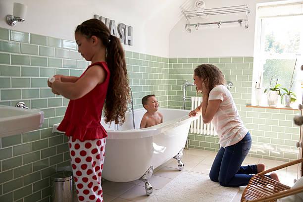 children having bath and brushing teeth in bathroom - kinderbadewanne stock-fotos und bilder