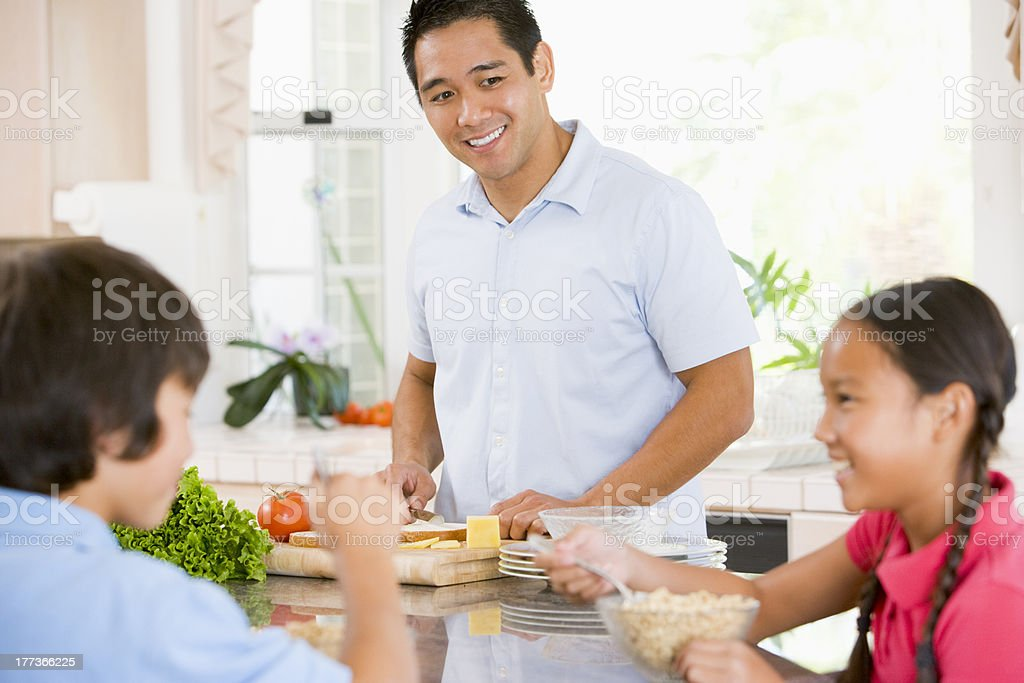 Children Having Breakfast While Dad Prepares Food royalty-free stock photo