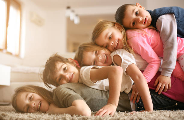 Children having fun at home. Large group of children lying at floor and having fun. Looking at camera. brother stock pictures, royalty-free photos & images