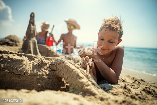 Children having fun building sandcastles on beach. Little boy is carving a sand bridge over a moat to his sandcastle. His siblings are building in the background. Nikon D850