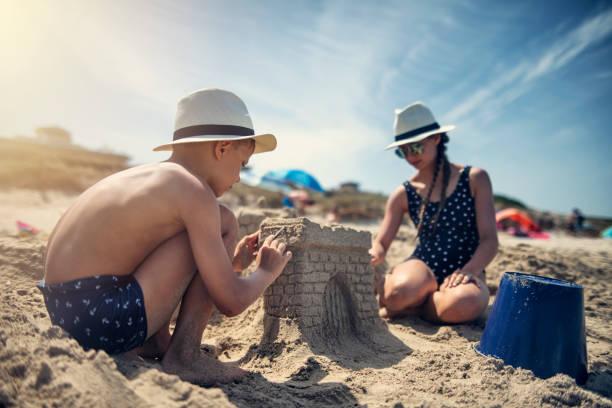 enfants ayant l'amusement construisant des châteaux de sable sur la plage - chateau de sable photos et images de collection