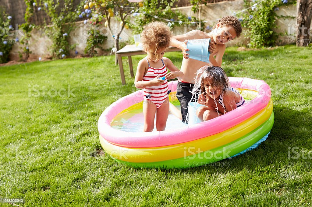 Children Having Fun In Garden Paddling Pool stock photo
