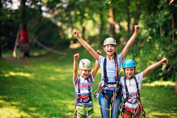 Children having fun in ropes course adventure park stock photo