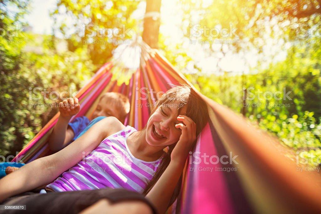 Children having fun on hammock on summer day stock photo