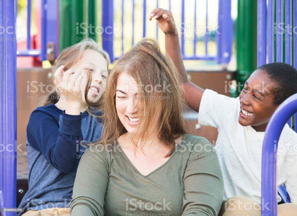 Children having fun with hair of mother stock photo