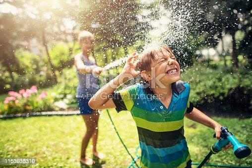 Little boy is splashed by his sister. Kids having garden hose duel. Sunny summer day. Nikon D810