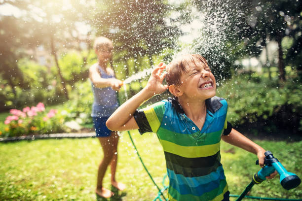 Children having garden hose fun in back yard Little boy is splashed by his sister. Kids having garden hose duel. Sunny summer day. Nikon D810 hose stock pictures, royalty-free photos & images