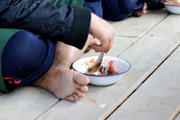 kinderen die na de lunch in aziatische school zittend op de vloer - midden amerika stockfoto's en -beelden