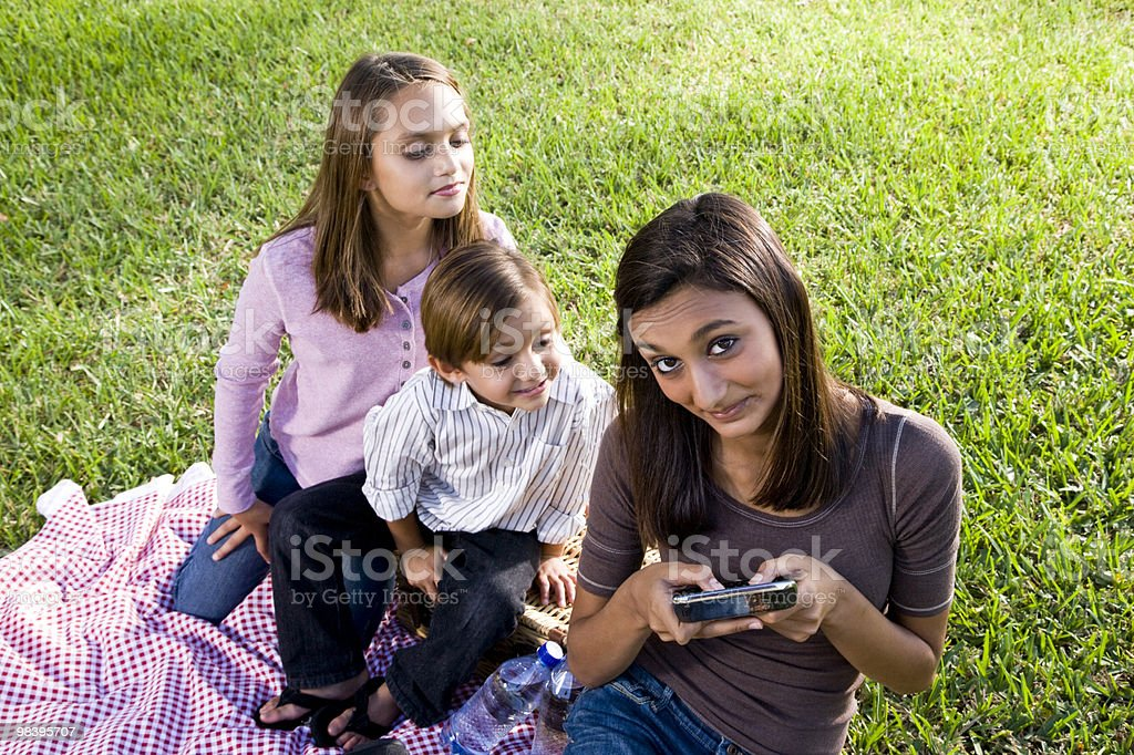 Children having picnic in park, teen girl texting royalty-free stock photo