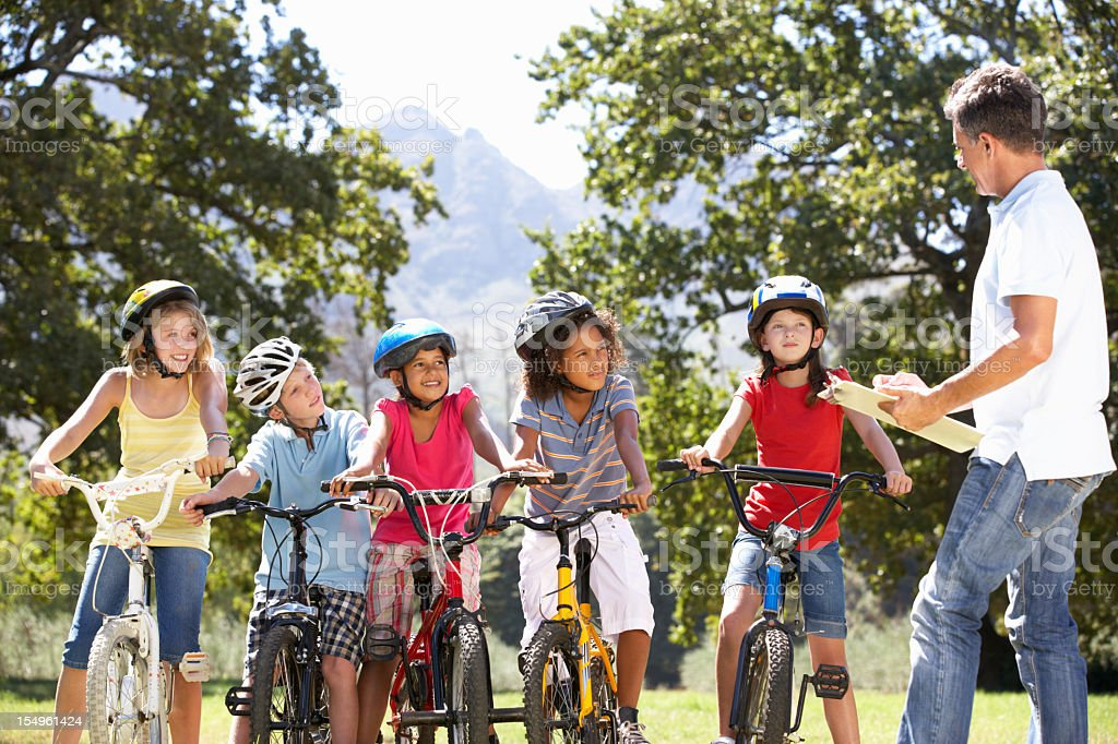 Children Having Safety Lesson From Adult Whilst Riding stock photo