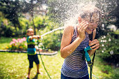 Little boy is splashing his sister with garden hose. Sunny summer day.\nNikon D810