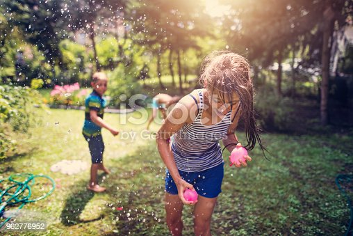 Little boy is throwing water balloons his sister. The girl is running for cover holding two water balloons Nikon D810