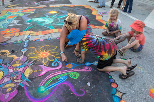 Children help artist with her street art work at Lake Worth Street Painting Festival stock photo