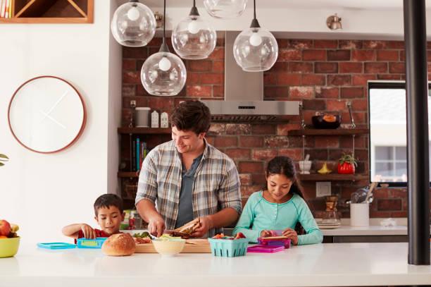 kinder helfen vater machen schulessen in küche zu hause - kochinsel stock-fotos und bilder