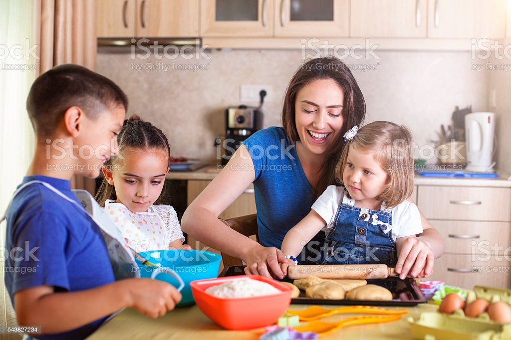 Children helping mother baking cookies stock photo