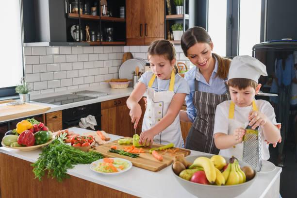 Kinder helfen Mutter in der Küche zubereiten leckeren Salat. Gesunde frische hausgemachte Speisen. Chöre für Kinder. – Foto