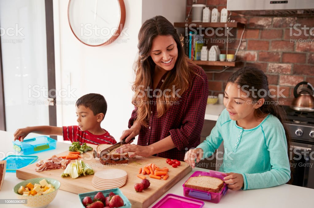 Children Helping Mother To Make School Lunches In Kitchen At Home stock photo