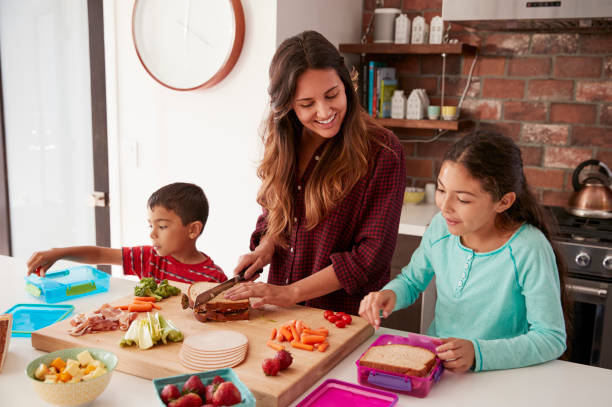 Children Helping Mother To Make School Lunches In Kitchen At Home Children Helping Mother To Make School Lunches In Kitchen At Home preparing food stock pictures, royalty-free photos & images