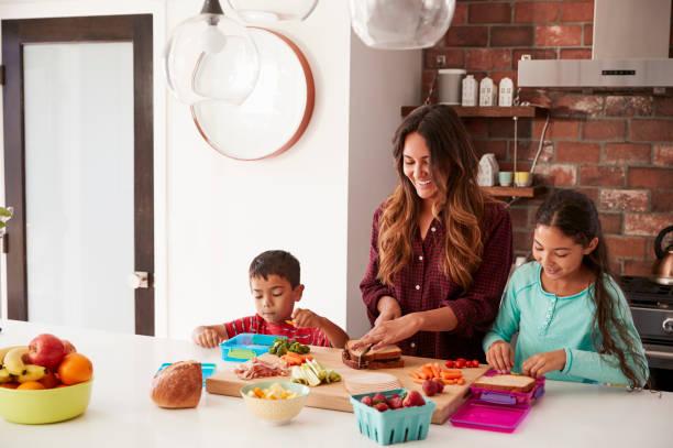 kinder helfen mutter machen schulessen in küche zu hause - kochinsel stock-fotos und bilder