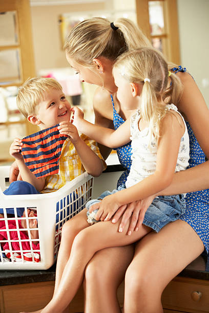 Children helping mother with sorting out laundry chore Mother And Children Sorting Laundry Sitting On Kitchen Counter Looking At Each Other Laughing little girls in panties stock pictures, royalty-free photos & images