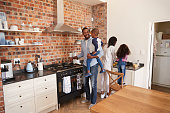 Children Helping Parents To Prepare Meal In Kitchen