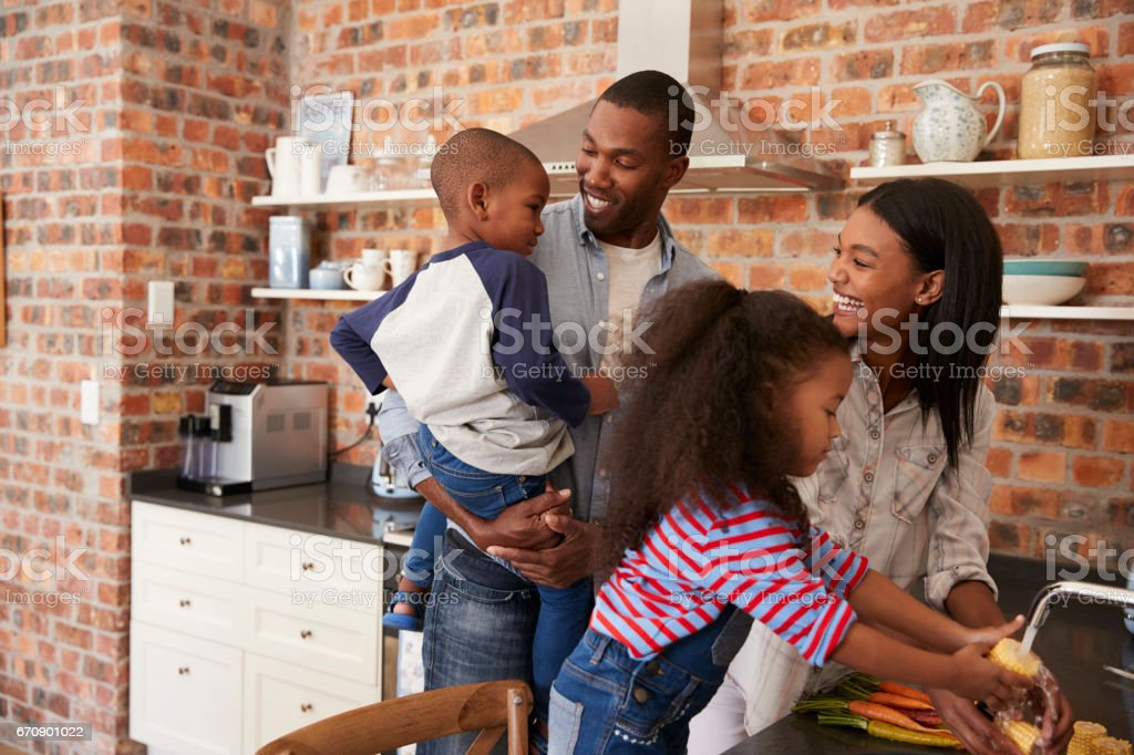 Children Helping Parents To Prepare Meal In Kitchen stock photo