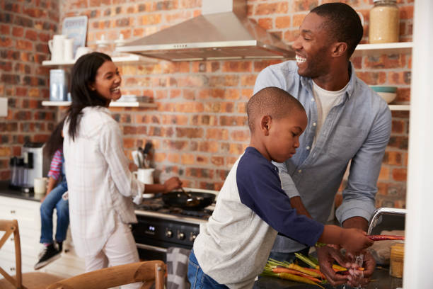 children helping parents to prepare meal in kitchen - home cooking stock photos and pictures