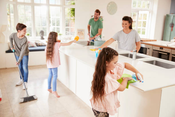 children helping parents with household chores in kitchen - clean stock pictures, royalty-free photos & images