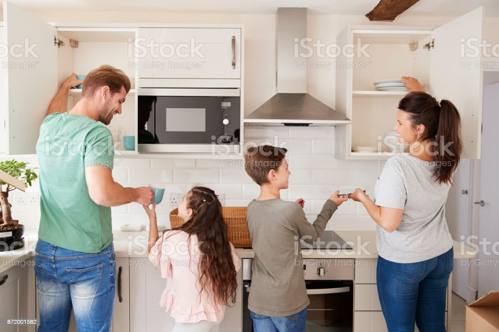 Children Helping To Put Away Crockery In Kitchen Cupboards stock photo