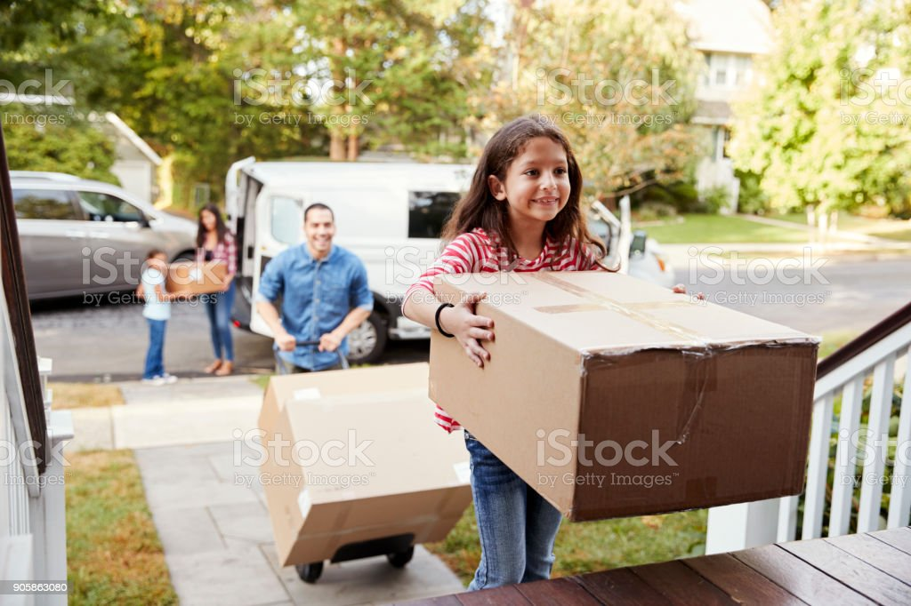 Children Helping Unload Boxes From Van On Family Moving In Day stock photo