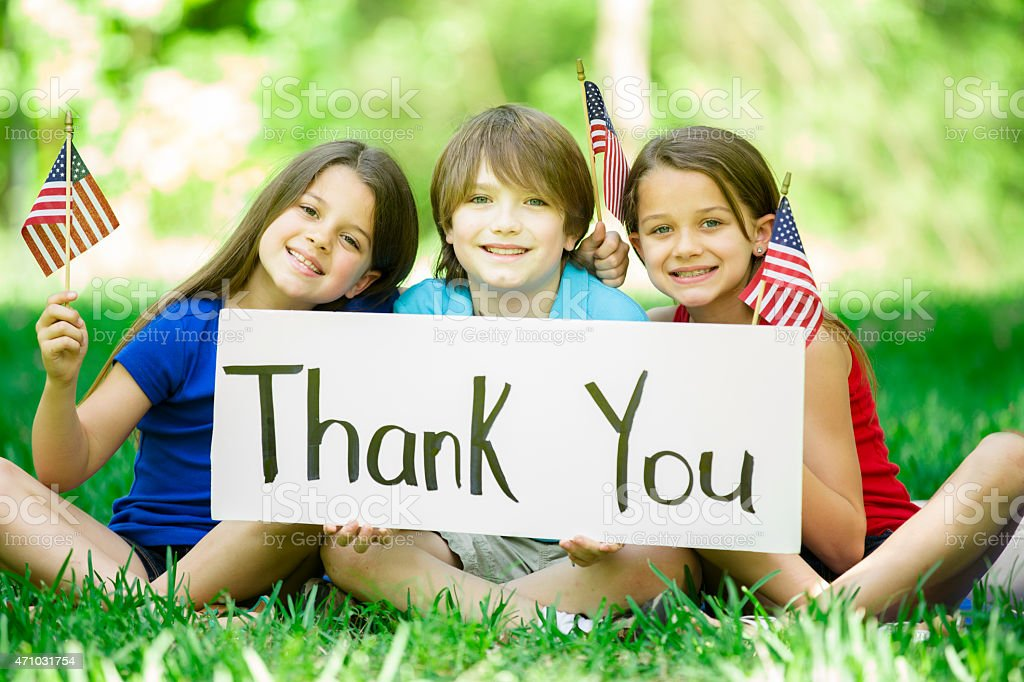 Children hold 'Thank You' sign with American flags. Memorial Day. stock photo
