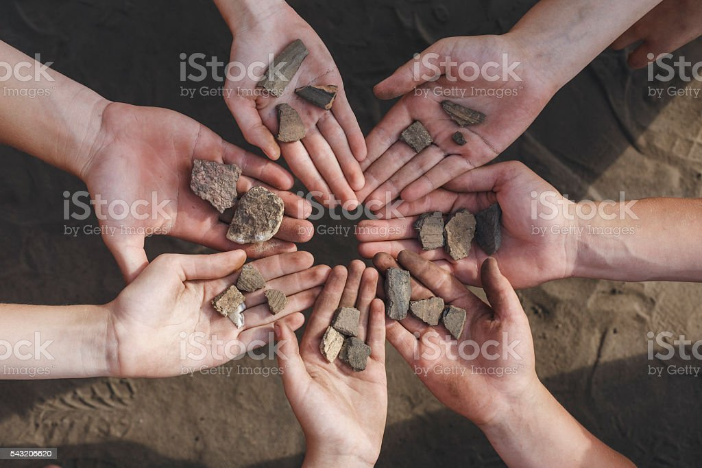 Children holding archaeological finds stones stock photo