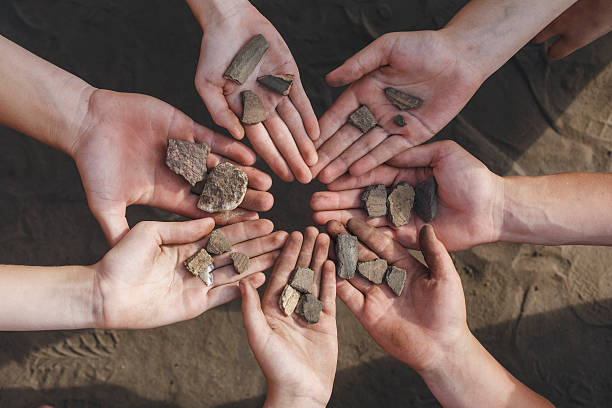 Children holding archaeological finds stones The children are holding the archaeological finds of stones and the age of seven thousand years ago. Children help in the excavation of human settlements. archaeology stock pictures, royalty-free photos & images