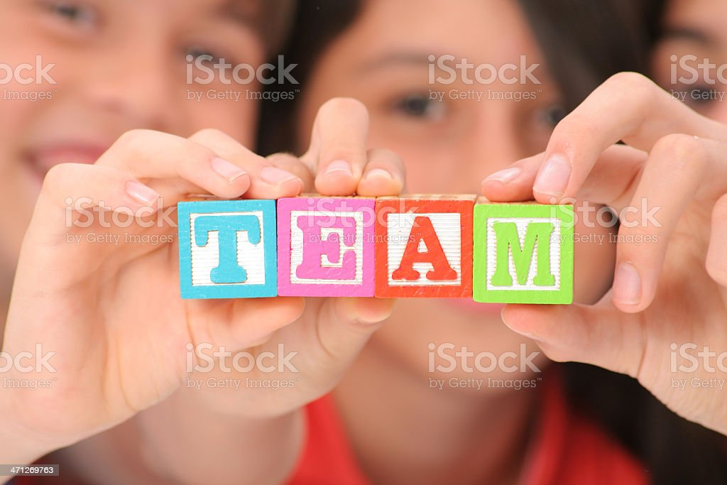 Children holding colorful blocks spelling the word team stock photo