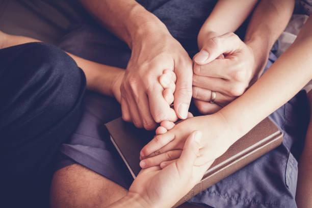 Kinder halten Hände und beten mit ihren Eltern zu Hause, Familie beten, Glauben und Hoffnung haben. – Foto