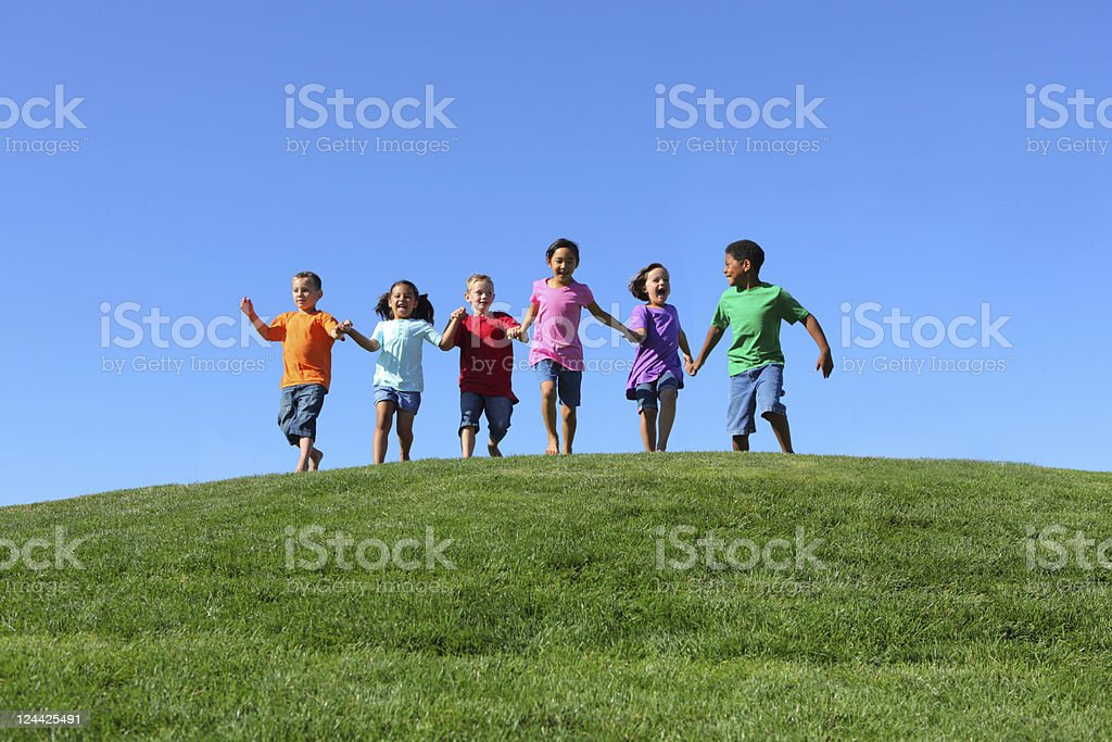 Children holding hands and running over hill royalty-free stock photo